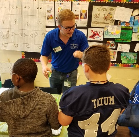 A Clorox employee leads Atlanta-area students in science experiments